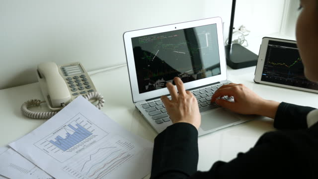 Businesswoman looking on Financial Charts in Document paper and Laptop screen, 4K(UHD)