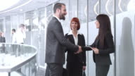 DS Businesswoman meeting with colleagues in corporate hallway