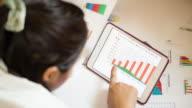 Businesswoman nalyzing market data information on a digital tablet