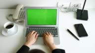 Donna d'affari aperto portatile e digitando sul Notebook con schermo verde in ufficio scrivania, 4 k (UHD)
