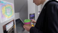 Businesswoman paying at ticket machine