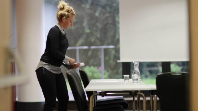 Businesswoman preparing meeting room