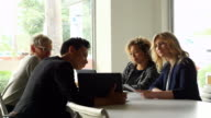 MS Businesswoman presenting project ideas to colleagues at conference table in office