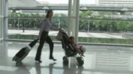 MS TS Businesswoman pushing daughter (2-3) sitting in baby stroller through lobby / Bangkok, Thailand