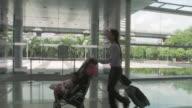 MS PAN Businesswoman running, pushing daughter (2-3) in baby stroller through lobby / Bangkok, Thailand