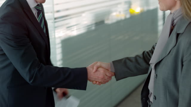 Businesswoman shaking hands with a male colleague in the hallway