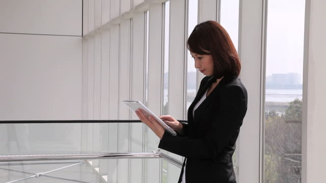 MS Businesswoman standing and typing to mobile computing / Odaiba, Tokyo, Japan