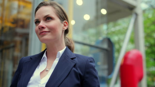 CU Businesswoman standing in front of office building, smiling / London, UK