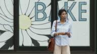 MS Businesswoman standing on street using mobile phone / New York City, New York, USA.