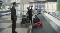 WS PAN ZI Businesswoman taking luggage from baggage claim carousel, then man gives her bouquet of flowers / Munich, Germany