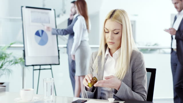 Businesswoman taking pill