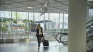 WS TS Businesswoman talking on mobile phone and walking with suitcase in airport / Munich, Germany