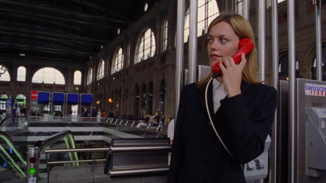 Businesswoman talking on pay phone near escalator / Zurich Train Station, Switzerland