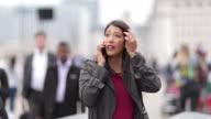 Businesswoman talking on smartphone on crowded street