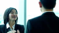 Businesswoman talking to her boss in office with glass windows background