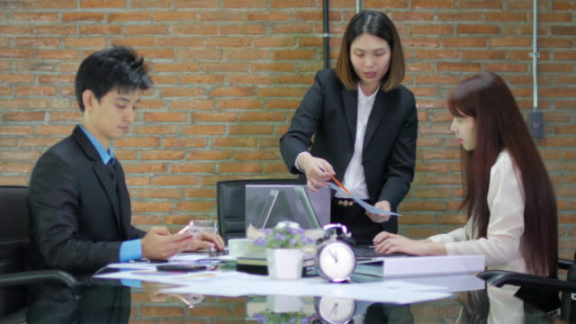 Businesswoman team leader checking and analyze graph of Her teammate , dolly shot left to right