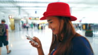 Businesswoman touching on smart phone while waiting for her flight