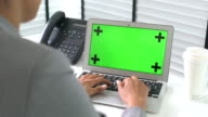 Businesswoman Typing on Laptop with green screen at Office