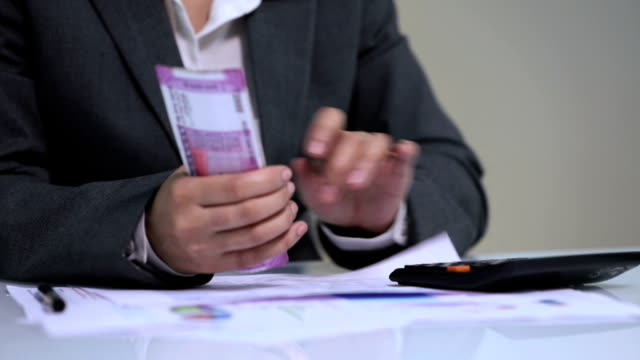 Businesswoman using a calculator and counting indian two thousand banknotes