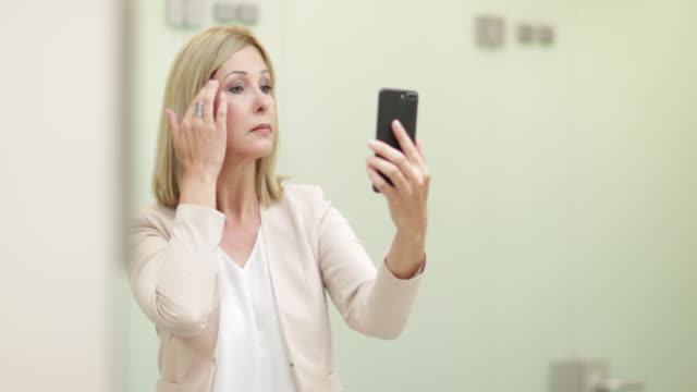 Businesswoman using a smartphone as a mirror