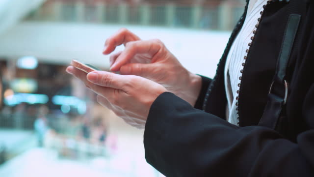 Businesswoman using smartphone  in elevator,shopping mall