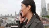 Businesswoman using smartphone looking out at London city skyline