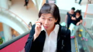 Businesswoman using smartphone on escalator in shopping mall,Slow Motion