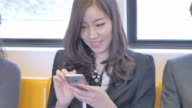 Businesswoman using smartphone on train,Close-up