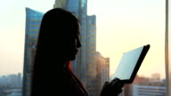 Businesswoman using tablet near the window at sunset period.
