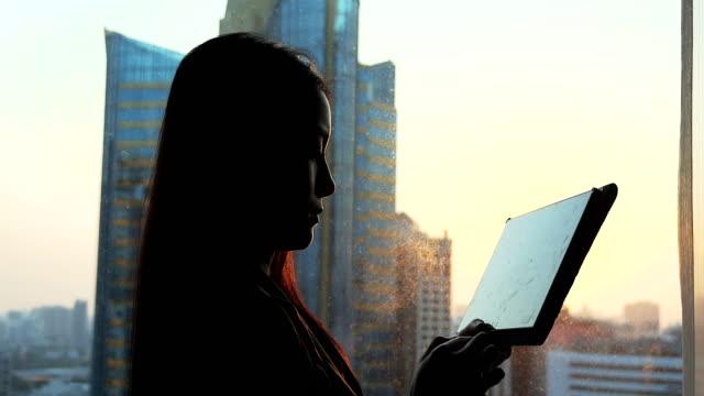 Zakenvrouw met behulp van Tablet PC in de buurt van het venster op zonsondergang periode.