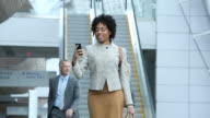 WS Businesswoman Video Conferencing on Cell Phone in Airport Lobby with Luggage / Virginia Beach, Virginia, United States