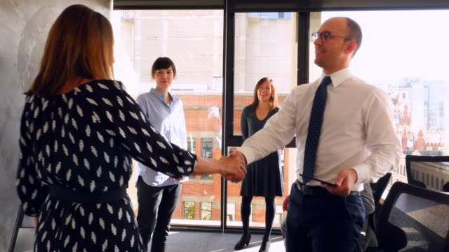 MS TS Businesswoman walking into meeting shaking hands with colleagues