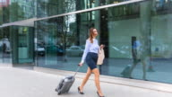 MS Businesswoman walking outdoors with trolley