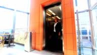 Businesswoman Walking Past Elevator in Modern Office Building.