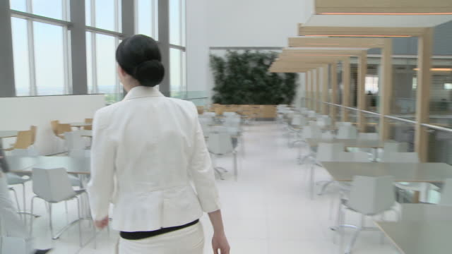 Businesswoman walking through canteen and shaking hands with businessman
