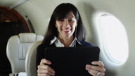 MS Businesswoman watching movie on digital tablet in airplane / Spanish Fork, Utah, USA