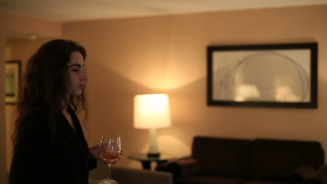 Businesswoman watching TV and enjoying a glass of wine