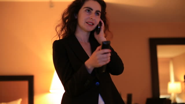 Geschäftsfrau vor dem Fernseher während am Telefon
