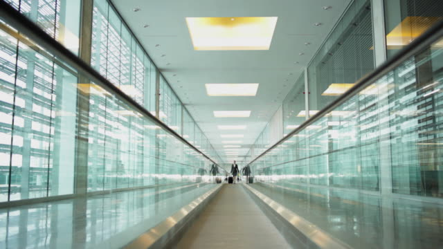 WS Businesswoman with case in airport on moving walkway / Toulouse, Haute-Garonne, France