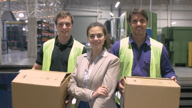 Businesswoman with manual workers carrying boxes