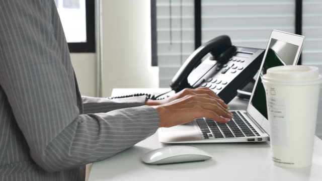 Businesswoman working at desk in office, Close up