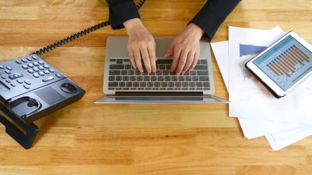 Geschäftsfrau Arbeiten in Schreibtisch mit Ihrem laptop mit einer Menge von Unterlagen und Finanzberichten, Hände Aufsicht