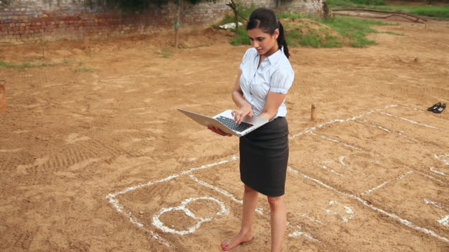 Businesswoman working on a laptop and playing hopscotch, Haryana, India