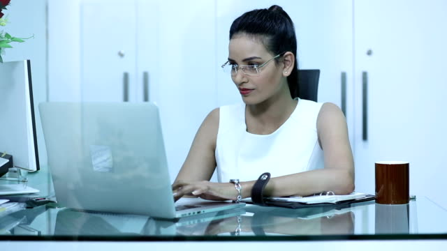 Businesswoman working on laptop in the office, Delhi, India