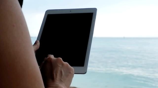 Geschäftsfrau, die Arbeiten auf dem Tablet PC am Strand
