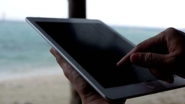 Geschäftsfrau arbeitet an Tablet-PC am Strand. Mädchen am Strand mit Tablet-PC arbeiten.
