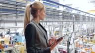 Donna d'affari lavorando su tavoletta fabbrica futuristico