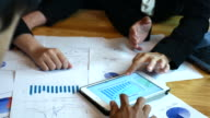 Businesswomen and Businessmen talking about financial analysis with tablet and printed charts