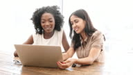 Businesswomen discussing over laptop at desk