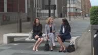 Businesswomen talking in a street bench in London